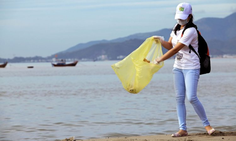 Junge Frau mit Mundschutz sammelt am Strand Müll in einer Plastiktüte. (Foto: Shutterstock)