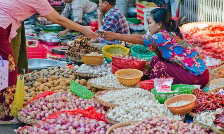 Straßenhändlerin umgeben von Lebensmitteln (Foto: Alamy)