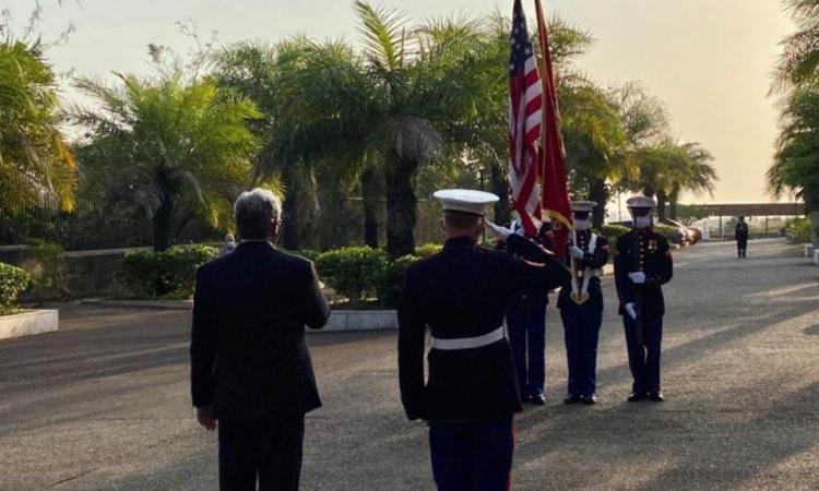 Le Chargé d'Affaires par intérim Steven Koutsis salue le drapeau américain.