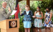 Ambassador Scott (L) administers the oath of office to Lott, flanked by her daughters.