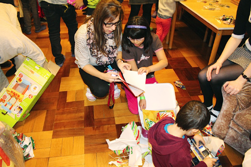 Kids open gifts from the Embassy community members.