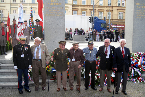 U.S. veterans pose for media in front of the Thank You America! memorial.