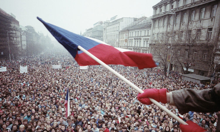Mladík drží českou vlajku nad zaplněným Václavským náměstí v listopadu 1989. (foto David Turnley/CORBIS)