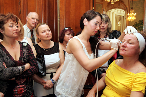 Participants of the seminar try the HydraFacial treatment on their own skin.