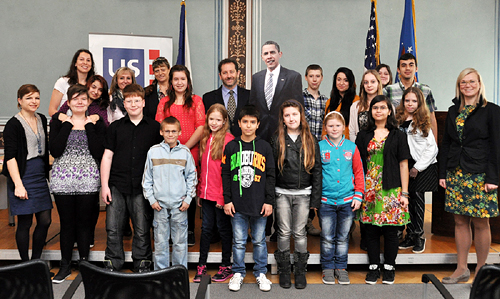 "Students from Obrnice Primary School and Deputy Chief of Mission Steven Kashkett at the opening of the exhibition ""America Is Not Just Burgers"" at the American Center."