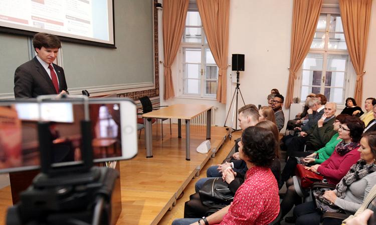 """Americký velvyslanec Andrew Schapiro předává ceny za tři vítězné fotografie soutěže """"Amerika Tvýma očima""""."""