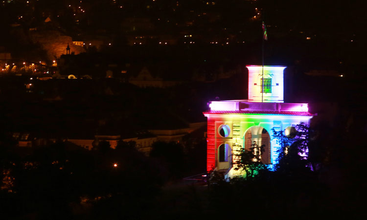 Gloriet velvyslanectví nasvícený duhovými barvami v době Prague Pride.