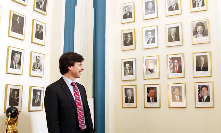 Ambassador Schapiro in front of photo portraits of the U.S. Ambassadors to the Czech Republic and Czechoslovakia at the U.S. Embassy Prague.