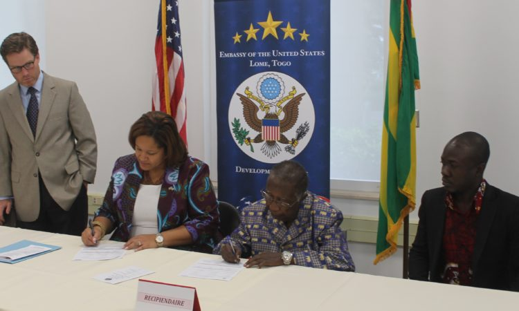 The Chargé d'Affaires Dana Banks signs a grant with one the recipients