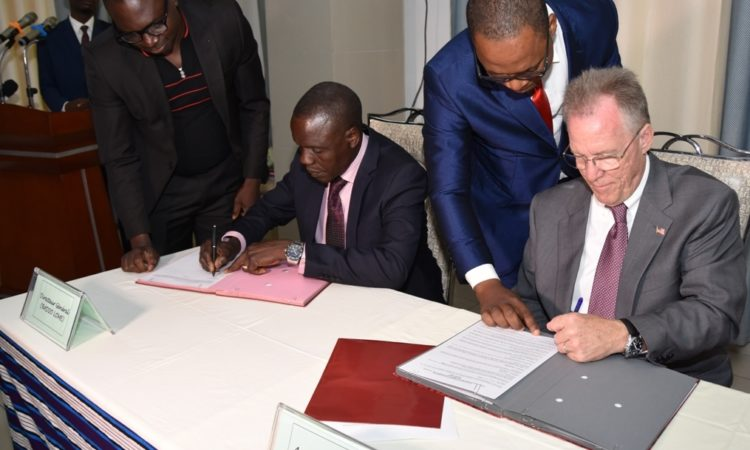Ambassador David Gilmour and Mr. John Takou Takouda director of Radio Lome sign convention for VOA