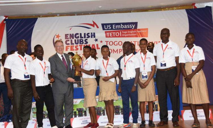 Ambassador handing the trophy to wining team