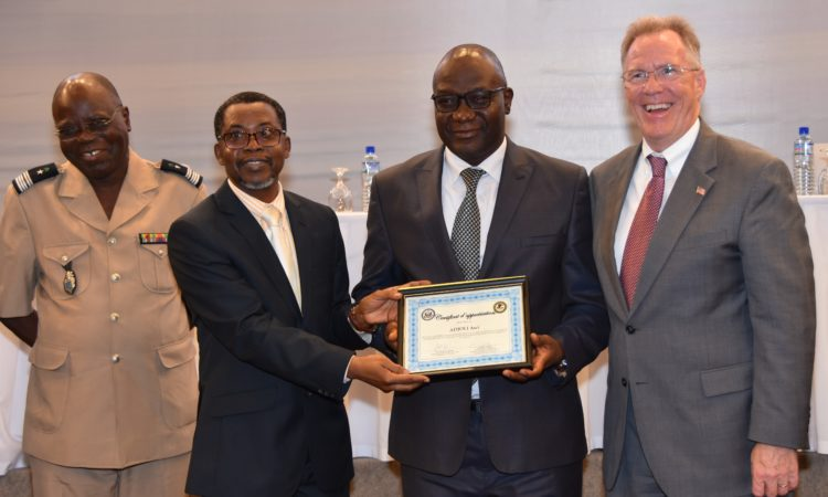 Magistrate and judicial police officer pose with Togo's Minister of Justice and Ambassador David Gilmour