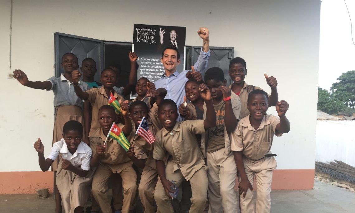 Mike Pryor Directeur des Affaires Publiques Posant avec les élèves devant une exposition de photos.