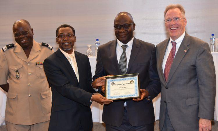 Un magistrat et un officier de la police judiciaire posent avec le ministre de la justice du Togo et l'ambassadeur David Gilmour