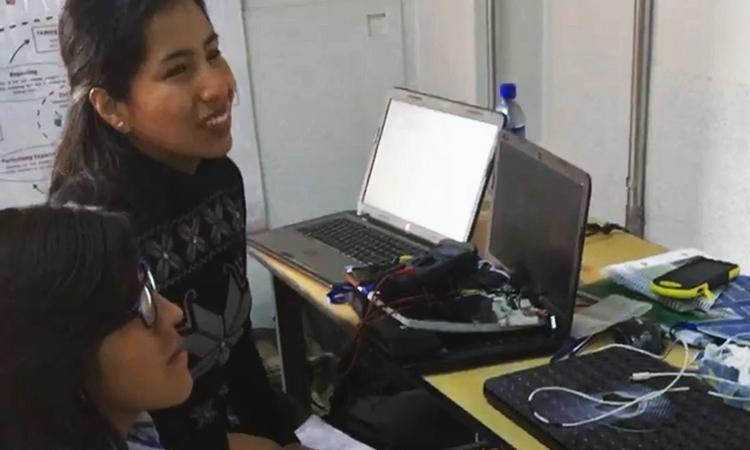 Dos jóvenes programadoras trabajan en sus computadoras y con sus equipos