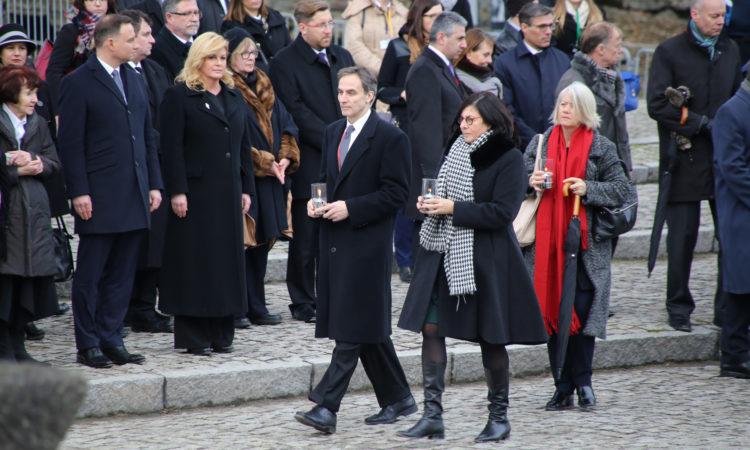 Ambasador Paul Jones zapala znicz pod Międzynarodowym Pomnikiem Ofiar Obozu w Birkenau.