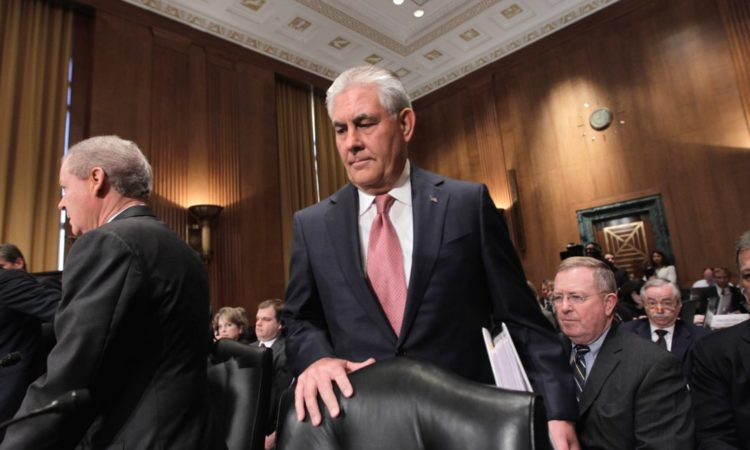Secretary Tillerson standing next to a chair