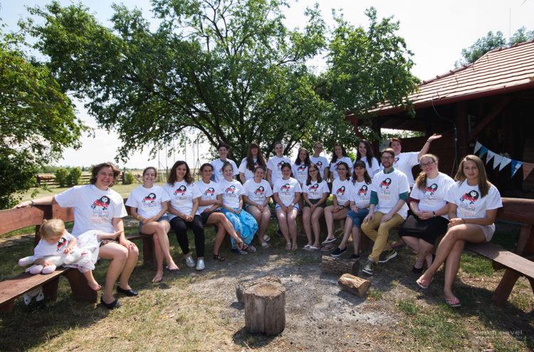 big half circle of two dozen teenage girls in white tops