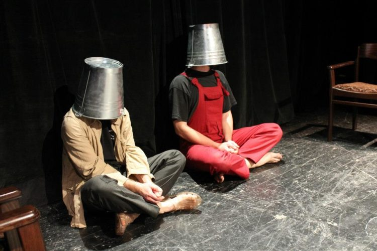 to men sitting on the floor with bucket on the head covering the face