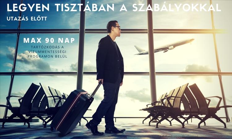 egy jólöltözött szemüveges férfi bőröndöt húz a reptéren