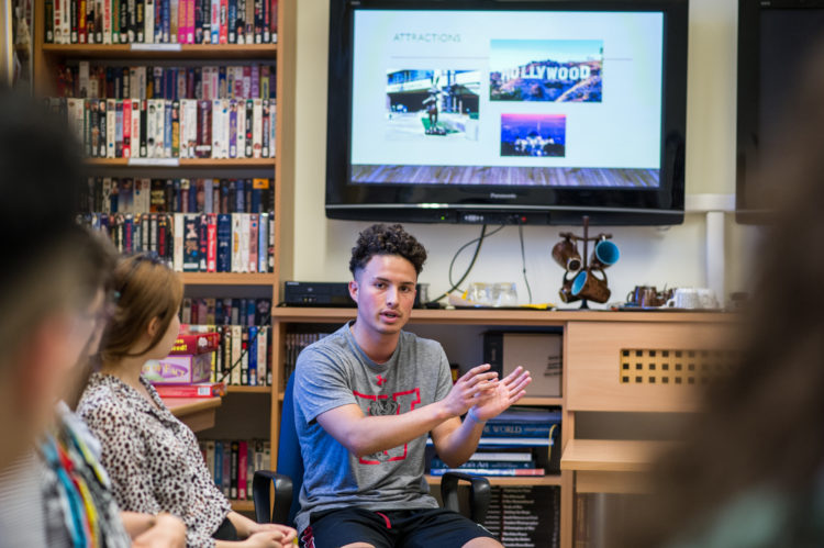 a young man talking and gesturing in front of a TV screen, sitting in front of a couple of people looking on