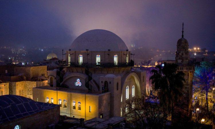 Emberek vonulnak ki és be a Damaszkuszi kapun, miközben balra fent, a felhős égbolton a Sziklatemplom látszik Jeruzsálem óvárosában. (© AP Images)