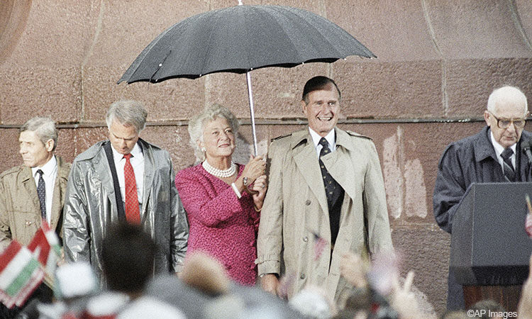 First Lady Barbara Bush holds an umbrella for President Bush as Hungarian President Bruno Straub speaks during the welcoming ceremony in Budapest in 1989. (AP Photo/Charles Tasnadi)
