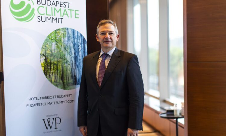 Chargé Dillard standing in front of the Budapest Climate Summit banner