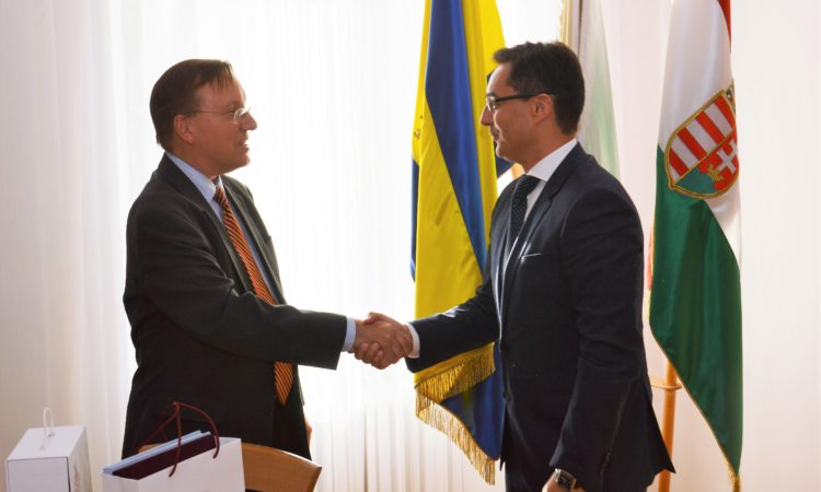 two men shaking hands in front of flags