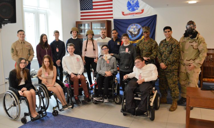 group phot of marines and high school students, some of whom are in wheel chairs