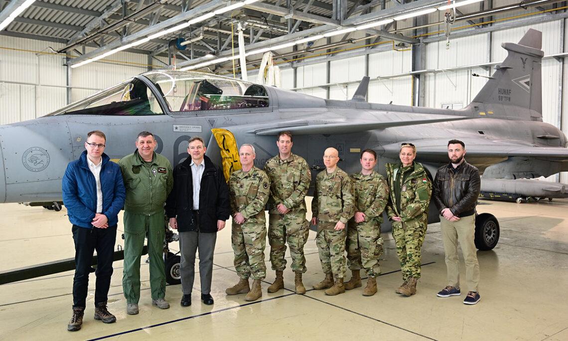 Csoportkép: 9 ember áll egy katonai repülőgép előtt