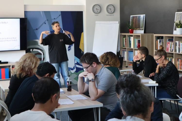 A résztvevők asztalok körül ülnek, előttük az előadó magyaráz.