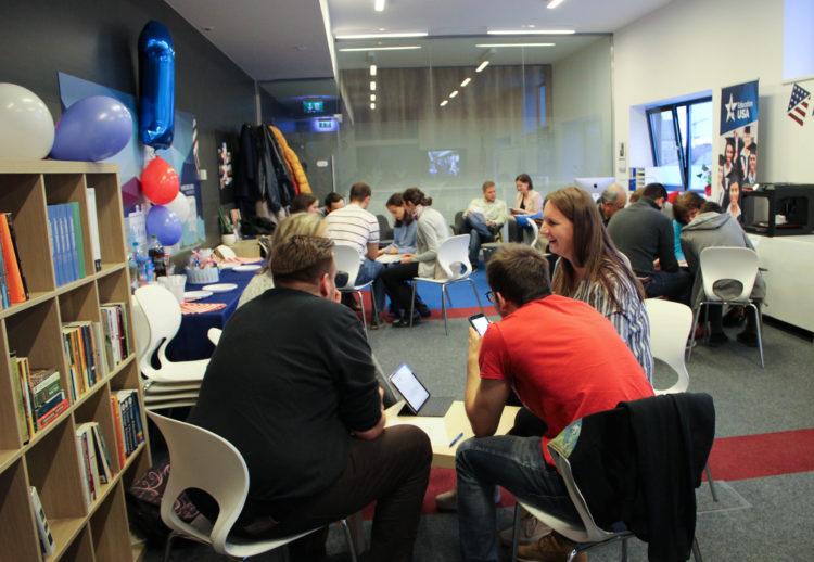 Beszélgető fiatalok ülnek asztalok körül a Kuckóban.