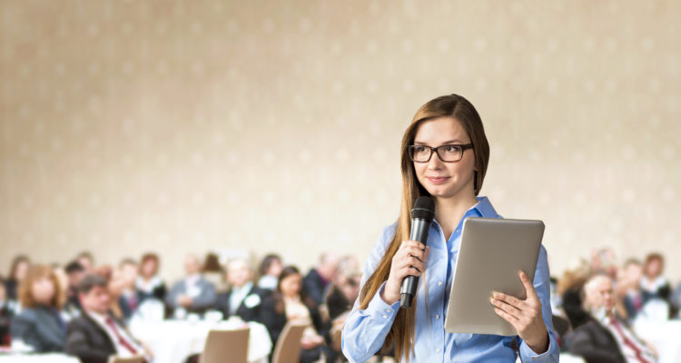 business woman is speaking on conference with microphone and ipad in hand