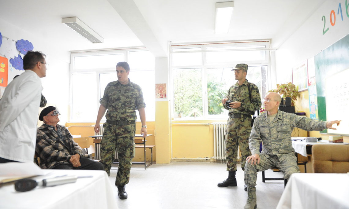 Four military medical doctors examining an elderly man