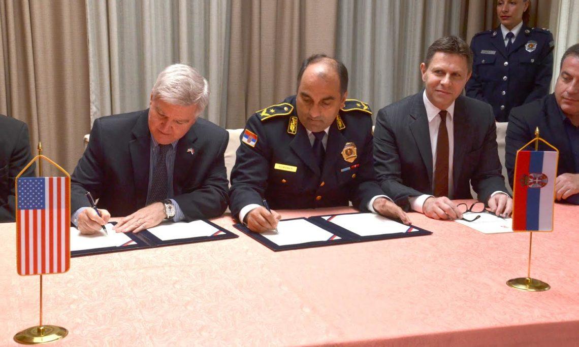 three man sitting behind a desk signing documents