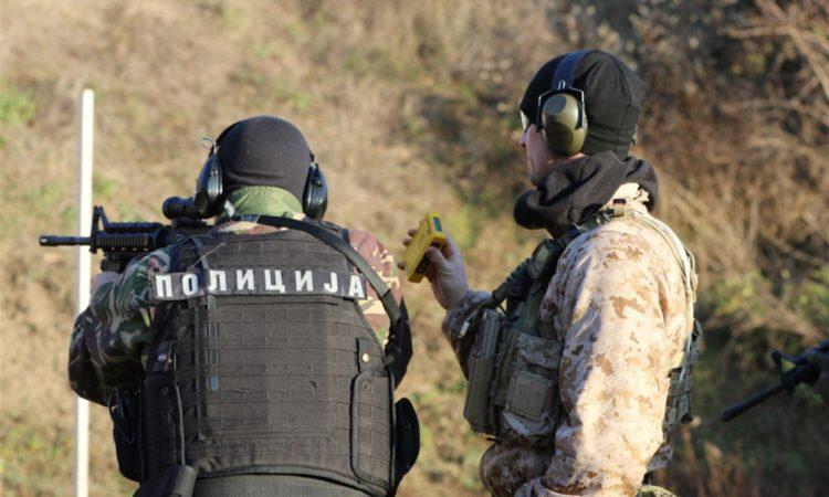Two men in uniforms on a gun range