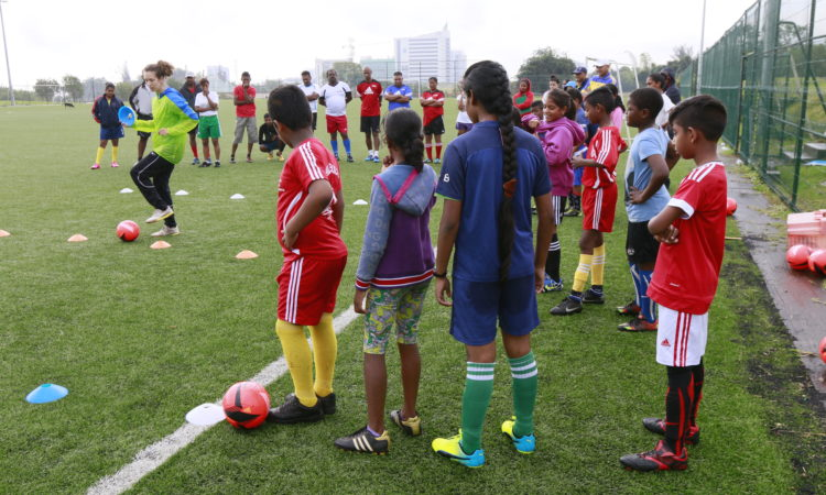 Kids listening carefully to the instructions of soccer envoy Kelsey Perlman.