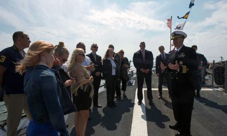 Cmdr. Kevin Hoffman, executive officer, USS Jason Dunham (DDG 109) gives a tour of the ship to U.S. Ambassador Bruce J. Oreck and guests of the Embassy on July 4, 2015. (© State Dept.)