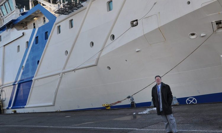 Man standing before a vessel (© State Dept.)