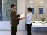 A man presents a certificate to a young woman
