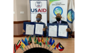 Regional Representative, USAID/ESC, Clinton White (left) and CEO, CDF, Rodinald Soomer show signed copies of the MOU which provides a broad framework for cooperation between the two entities.