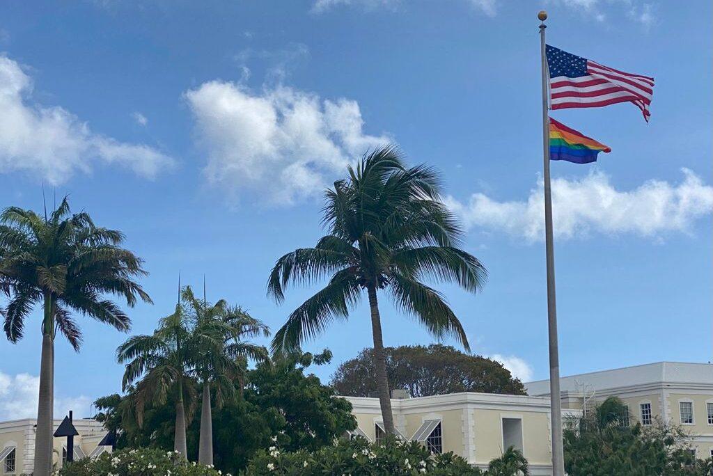 LGBTQ flag flying underneath the American flag