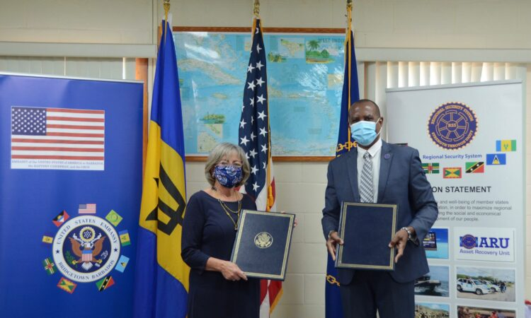 Two people standing in front of flags while holding documents