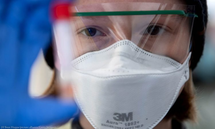 Person in face mask looking at test tube (© Sven Hoppe/picture alliance/Getty Images)