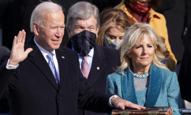 oe Biden con una mano alzada y la otra en la Biblia sostenida por Jill Biden (© Alex Wong/Getty Images)