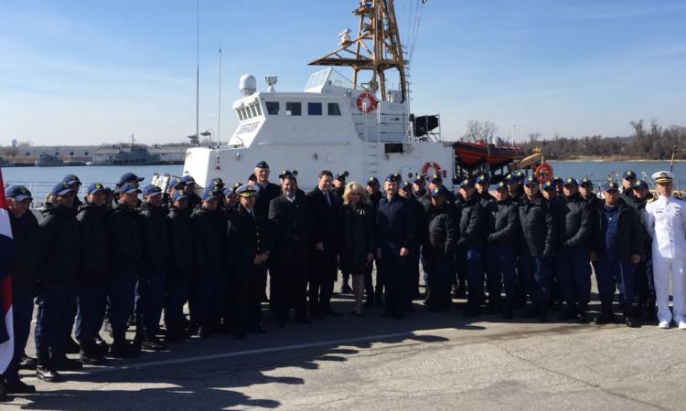 Un grupo de personas frente a un barco del Guardacostas.