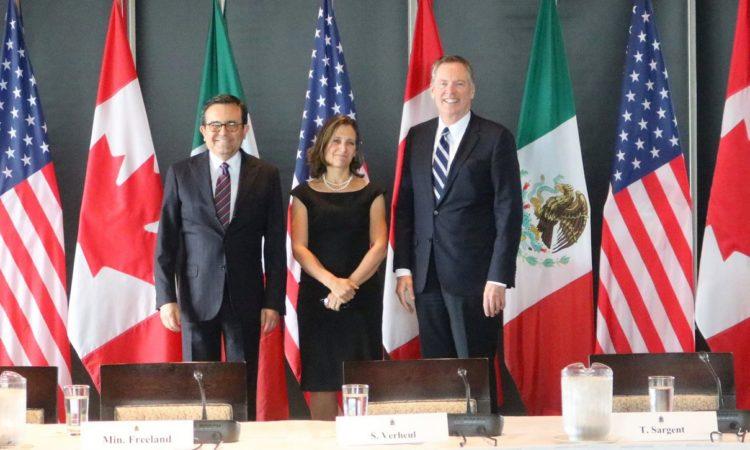 1 mujer y 2 hombres parados frente a las banderas de Canadá, México y Estados Unidos