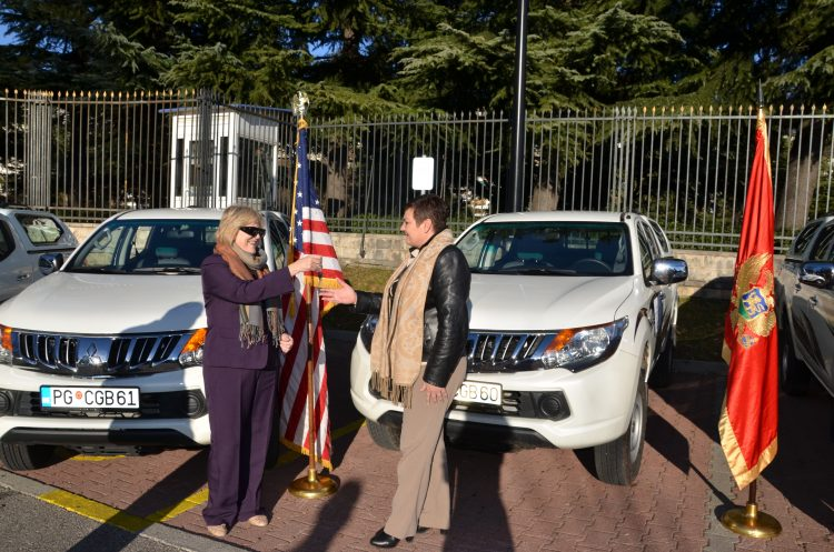 Two women standing in front of two cars and a flag, one handing keys to the other