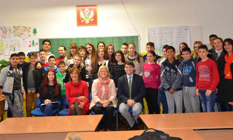 Ambassador and students posing for a family photo in the classroom